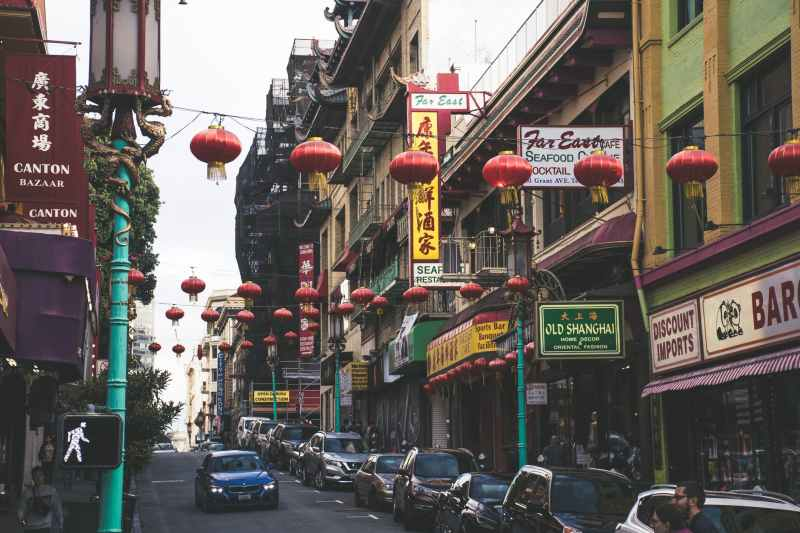 vehicles parked beside buildings under red chinese lanterns