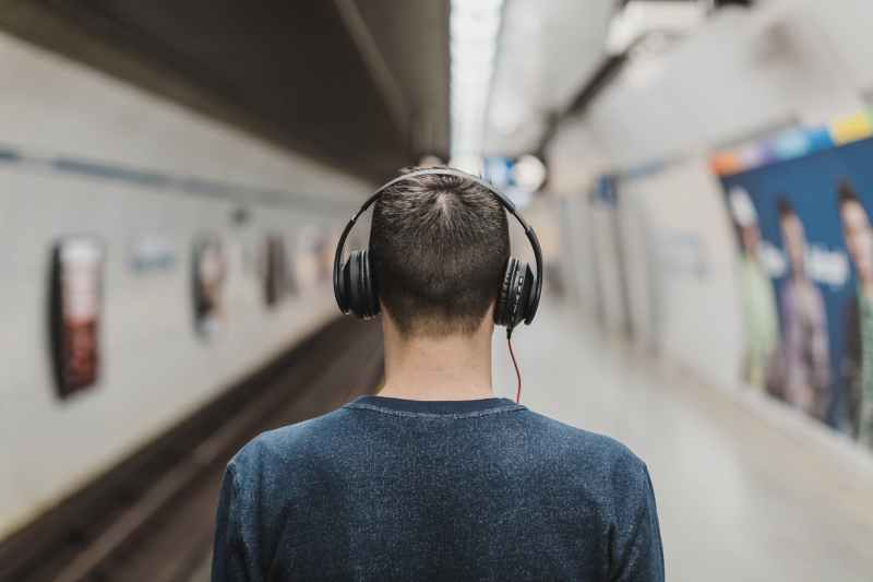 man wearing black headphones beside train rail